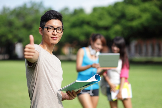 Smiling Asian student with thumbs up gesture on college campus lawn. College girls in blurred background.